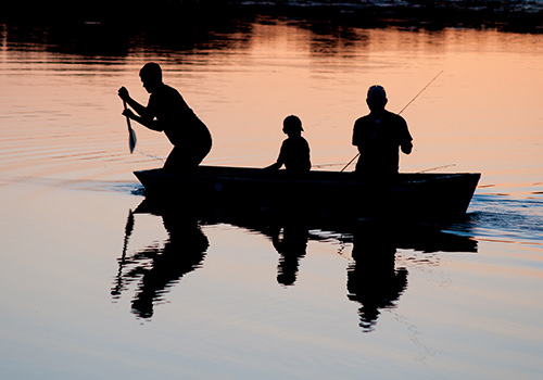 Photo a three people fishing inside a boat at dusk.